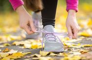 Hands tying trainers shoelaces on the autumn pave Stock Photos