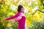 Portrait of a woman outdoors in a sportswear, hands outstreched Stock Photos