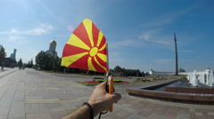 Macedonian tourist holding a waving flag and pov of Victory monument. Victory Stock Footage