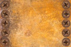 Aged and weathered rusty metallic panel with screws Stock Photos