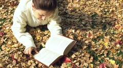 Young pretty woman reads a book. Autumn time Stock Footage
