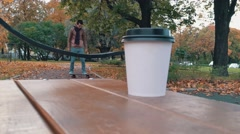 White paper cup with hot drink on the bench in autumn city park close up with Stock Footage