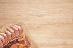 Smoked meat on a wooden table. Stock Photos