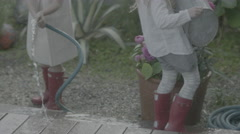 Young sisters spray water everywhere while trying to tend their garden. Stock Footage