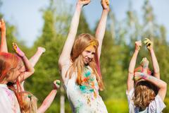 Girl smeared in colored powder dancing with friend Stock Photos