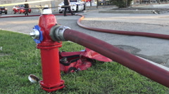 Water hydrant on the street in use with fire hose attached Stock Footage