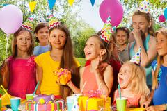 Group of excited kids congratulating birthday girl Stock Photos