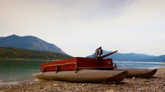 Time Lapse video. Raised view over small boat on gravel coast of mountain lake. Stock Footage