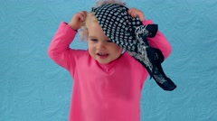 Cute child play hide and seek with head scarf Stock Footage