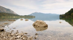 Time Lapse video of stone in water of mountain lake. Gentle waves on autumn lake Stock Footage