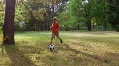 Young boy playing soccer in the park. Stock Footage