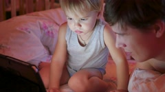 The little child with the father watching cartoons on a tablet in the evening Stock Footage