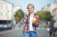 Portrait of young girl against blurred street, talking on phone Stock Photos