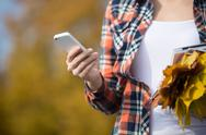 Female holding phone in hand, yellow leaves in another Stock Photos
