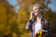 Portrait of young attractive student outsides, talking on her phone Stock Photos