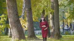 Portrait of young pregnant woman smiling - standing at autumn park Stock Footage