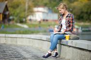Portrait of an attractive student girl sitting at bridge writing Stock Photos