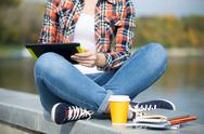 Student sitting turkish at bridge with tablet Stock Photos