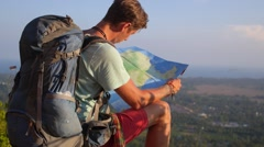 Lost Traveller with Backpack Explores Map on Mountain Peak Stock Footage