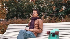 Young man with knitted scarf with skateboard sitting on bench in autumn park Stock Footage