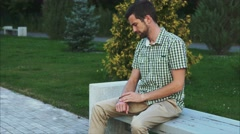 Casual dressed man sit on the bench in the park and use his modern smart watch Stock Footage