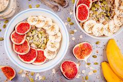 Healthy breakfast: oatmeal with fresh figs, bananas, pumpkin seeds, coconut a Stock Photos