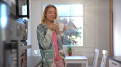 Attractive young woman drinking coffee and uses a smart phone  in the kitchen. Stock Footage