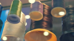 Rows spools of thread of different colors on a shelf in a store Stock Footage