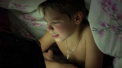 Boy lying under blanket and watching cartoons on touch pad Stock Footage