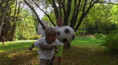 Boy beats a soccer ball head in slow motion. Stock Footage