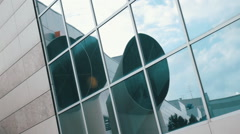 Three huge ventilation pipes and air conditioning units are reflected in a glass Stock Footage