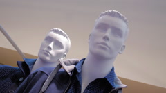 White mannequins exhibit a new collection of men's clothing in a large store Stock Footage