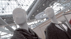 White glossy mannequins exhibit a new collection of women's clothing in a shop Stock Footage