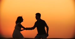 Young happy couple dancing wedding dance at sunset, slow motion Stock Footage