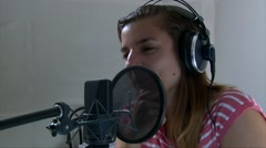 Teen girl sings at the professional audio studio into a microphone Stock Footage