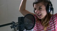 Girl emotionally singing hard rock song into the studio microphone Stock Footage