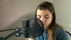 Girl speaking, emotionally reading text into a studio microphone Stock Footage