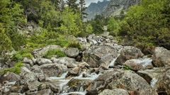 Summer timelapse of stream running through rocks in mountains, High tatras, Stock Footage