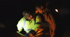 4k, Mechanic and customer looking at an engine of a broken down car late at nigh Stock Footage