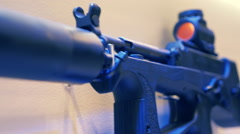 New tech automatic gun with sight and silencer on the wall Stock Footage