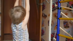 A small child is engaged in the gymnastic rings in indoor Stock Footage