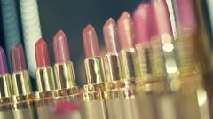 Lipstick variety of colors and shades on the store showcases sparkle in light Stock Footage
