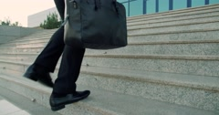 Businessman holding a business briefcase, climbing the stairs in the business Stock Footage