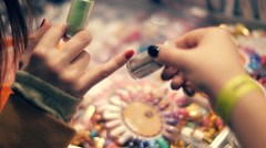 Girls sees a large collection of glitter in bottles, and chooses the right color Stock Footage