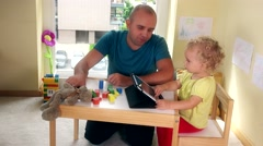 Father with smart phone and toddler girl playing with tablet computer Stock Footage