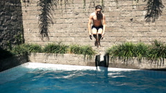 Young teenager jumping into swimming pool, super slow motion 240fps Stock Footage