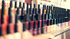 Rows of colorful bottles of nail polish on the showcase of store Stock Footage