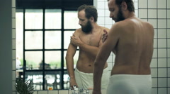 Young man in towel applying moisturizing cream on his arm in bathroom  Stock Footage