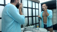 Young man applying moisturizing cream on his face in bathroom  Stock Footage
