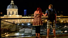 Young couple taking pictures to the Institut de France at night Stock Footage